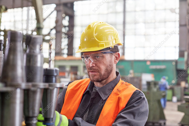 Focused worker examining steel parts