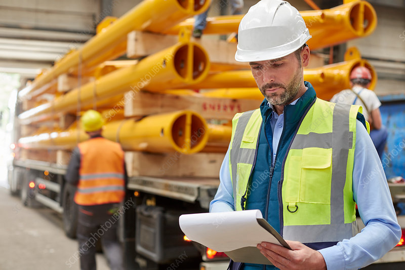 Male foreman reading paperwork on clipboard