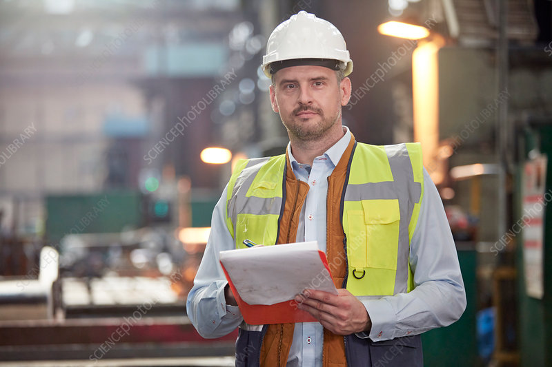 Portrait male foreman with clipboard in factory