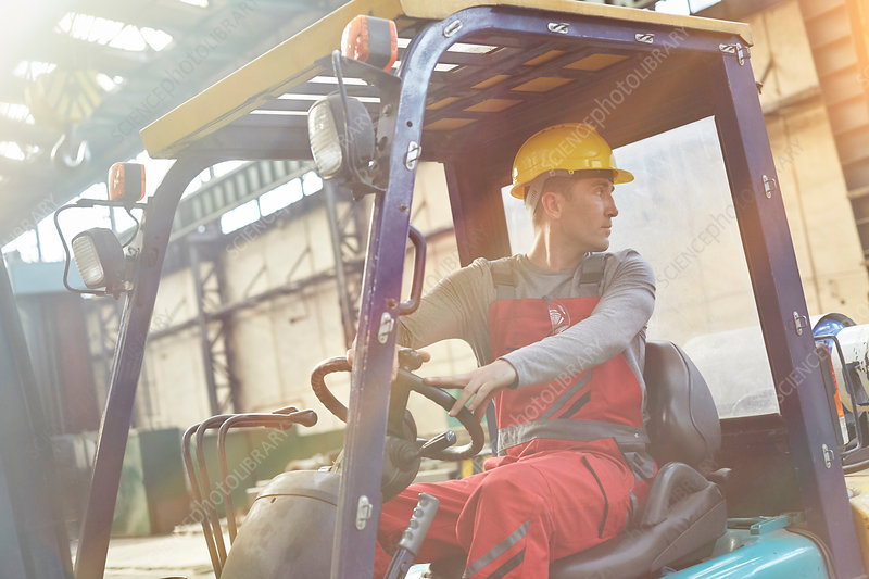 Male worker driving forklift, backing up