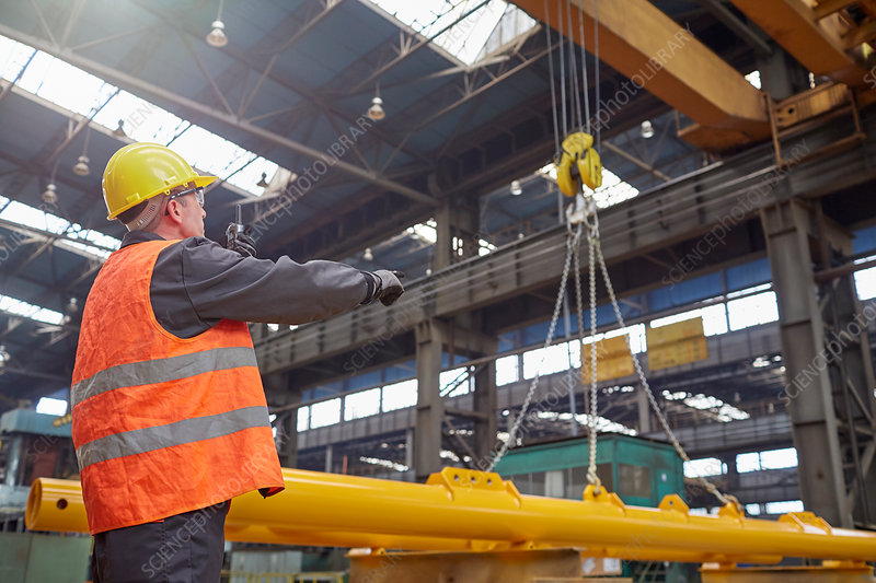 Male worker guiding hydraulic crane in factory