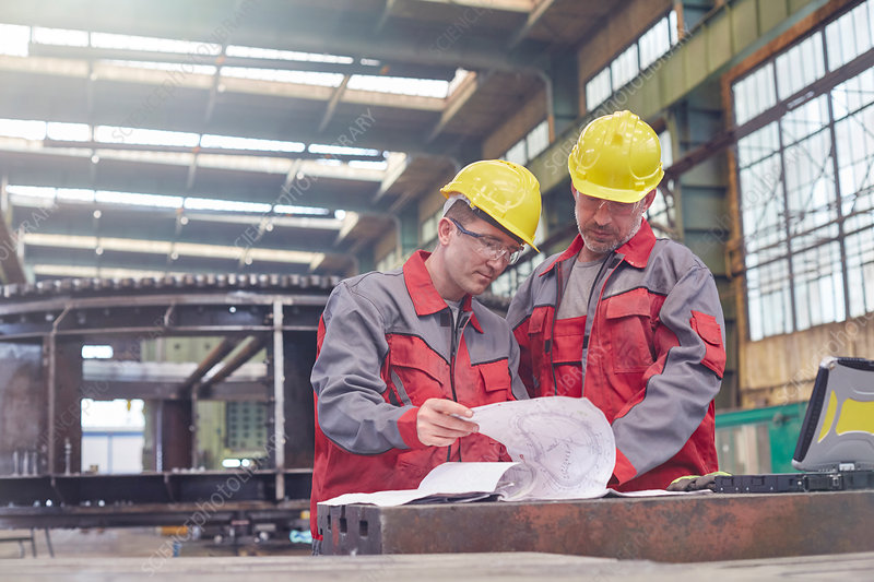Male engineers reviewing blueprints in factory