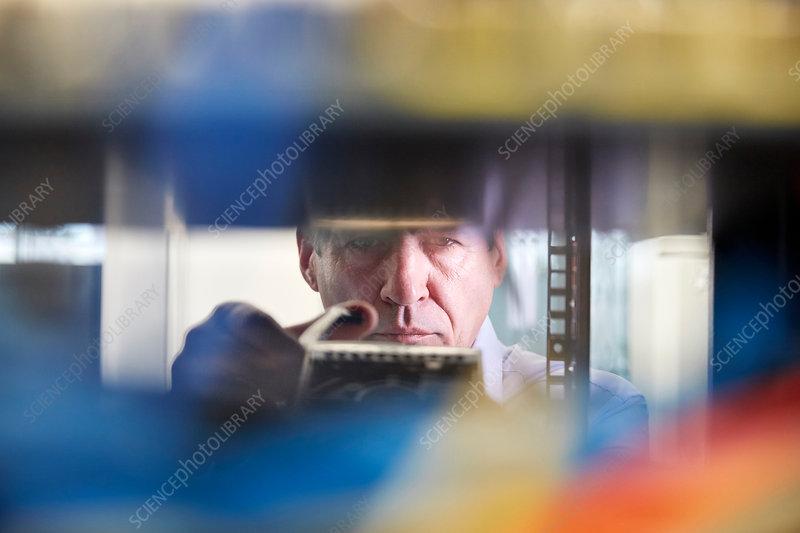 Focused male IT technician working in server room