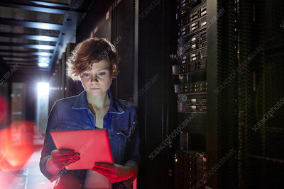 Focused IT technician using tablet in server room