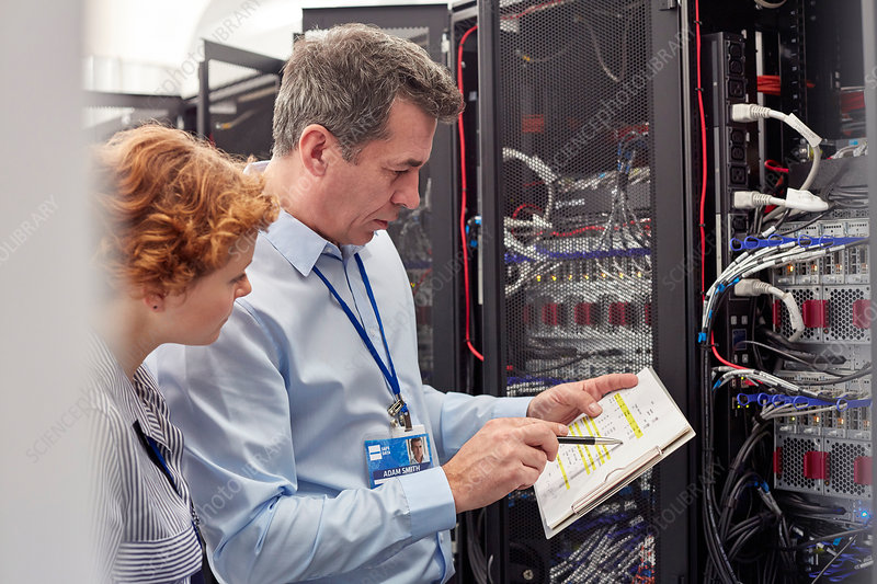 IT technicians examining panel in server room