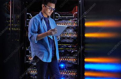Focused IT technician using tablet at panel