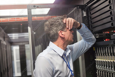 Frustrated IT technician at panel in server room