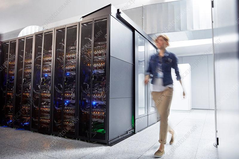 Female IT technician walking in server room
