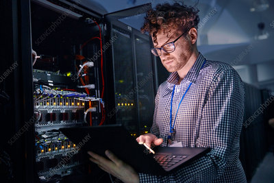 Focused IT technician working at laptop