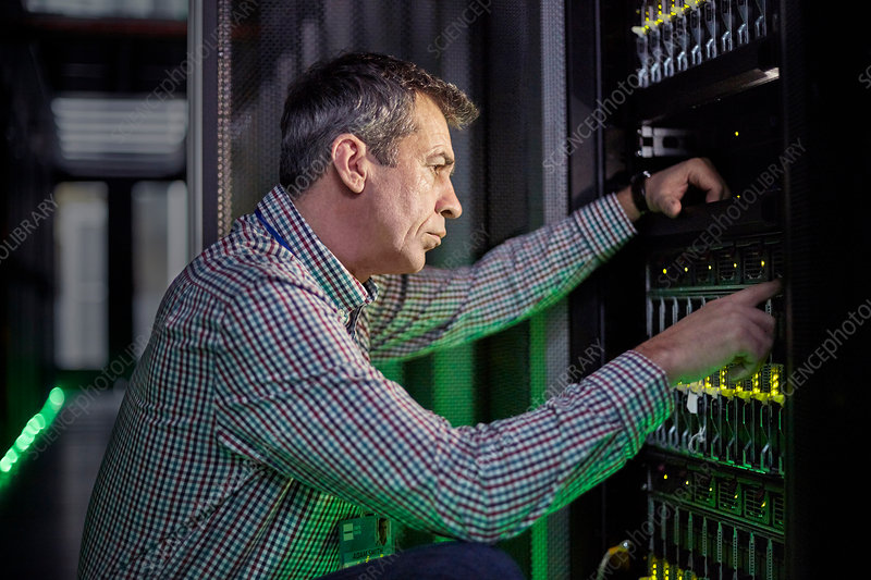 Focused IT technician working at panel