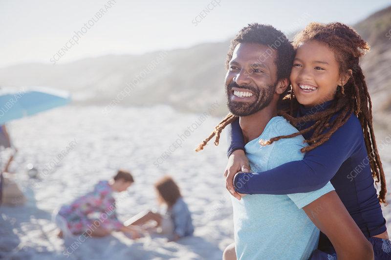 Smiling, father piggybacking daughter