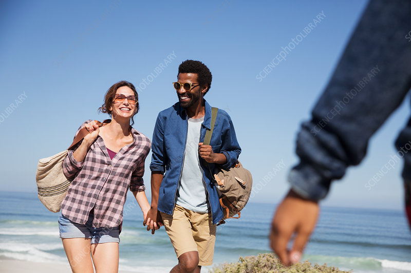 Smiling couple holding hands and walking