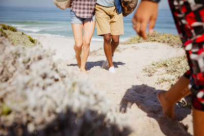 Legs of couple walking on beach path