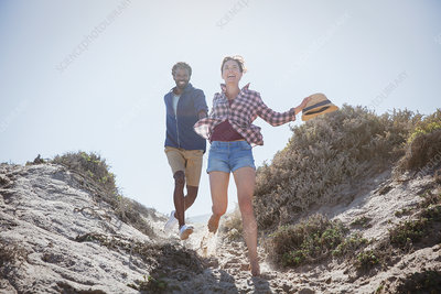 Playful, energetic couple running on beach path