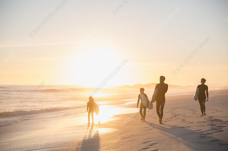 Silhouette family surfers walking on beach