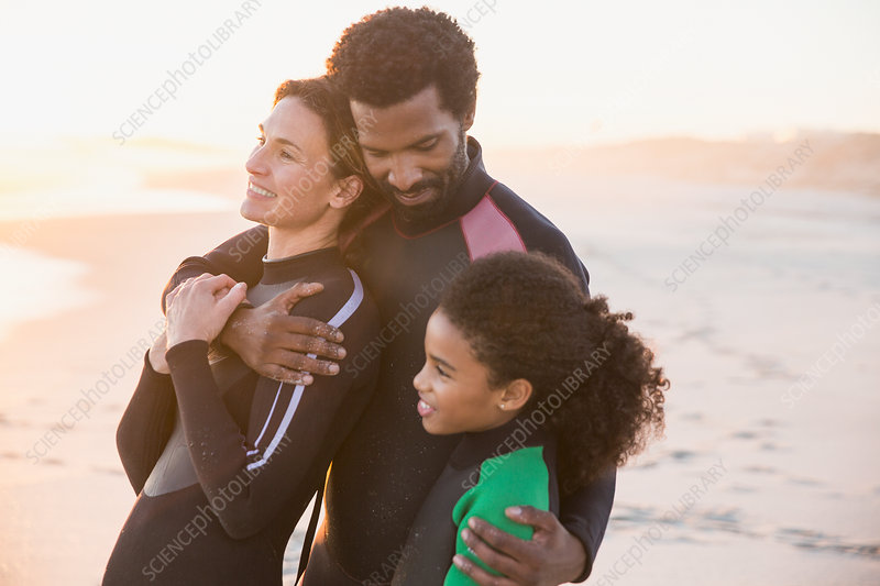 Affectionate family in wet suits hugging