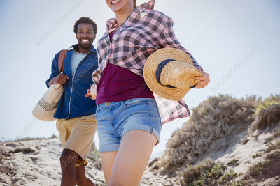 Smiling, enthusiastic couple walking on beach path