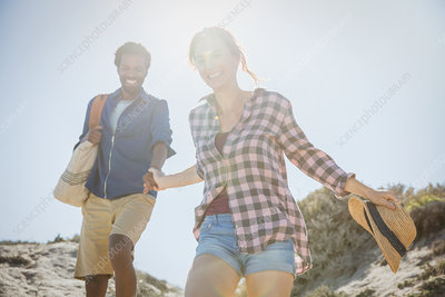 Smiling couple walking on beach path