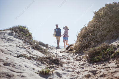 Couple walking on sunny summer beach path