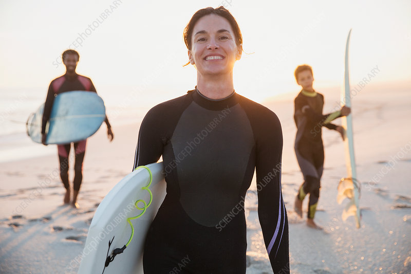 Portrait surfer in wet suit with family