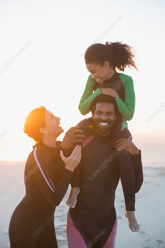 Happy family in wet suits on summer sunset beach