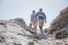 Affectionate couple walking up summer beach path