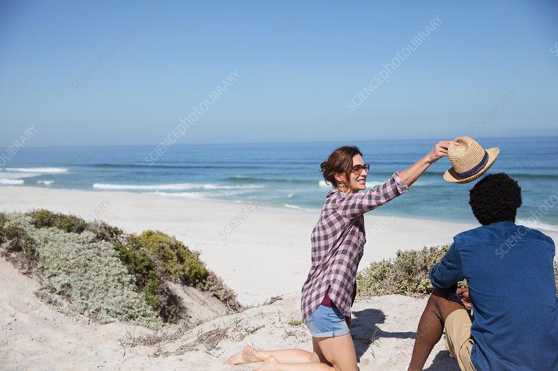Woman placing hat on boyfriend