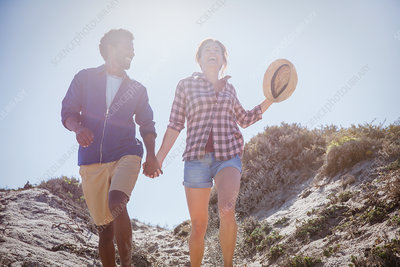 Multi-ethnic couple walking, holding hands path