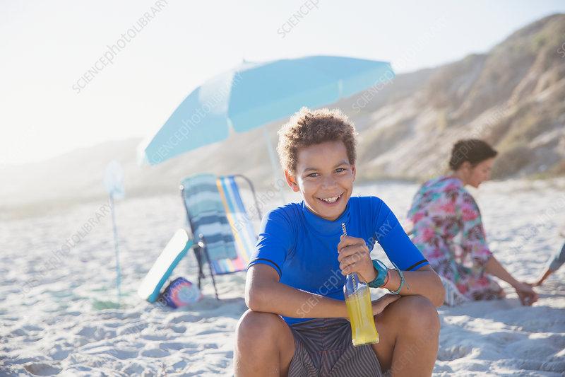 Portrait boy drinking juice on summer sunny beach