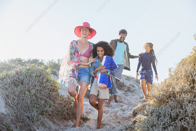 Family walking on sunny summer beach path