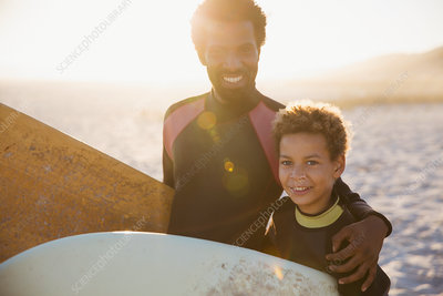 Portrait father and son in wet suits