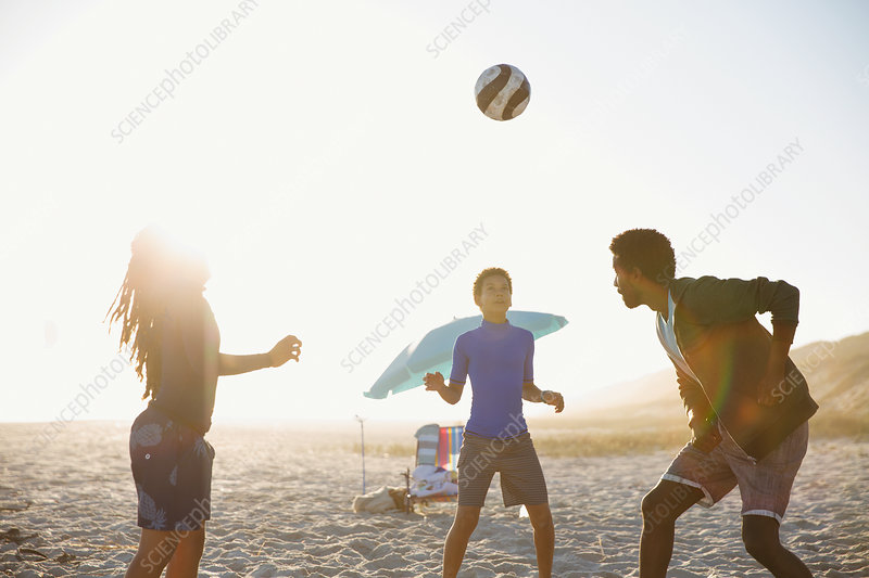 Family playing soccer on sunny summer beach