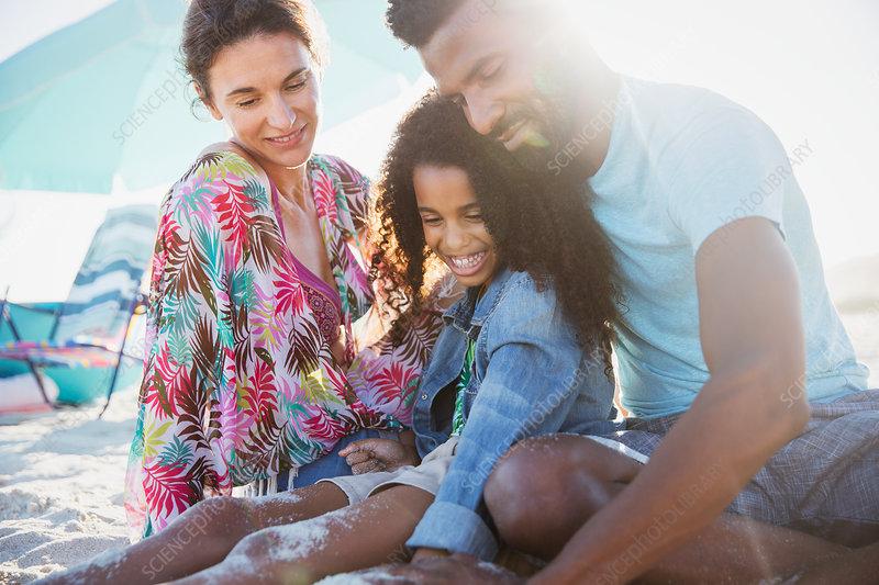Multi-ethnic family relaxing on sunny summer beach