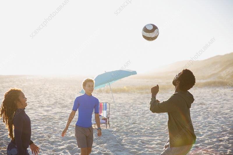 Father and children playing soccer