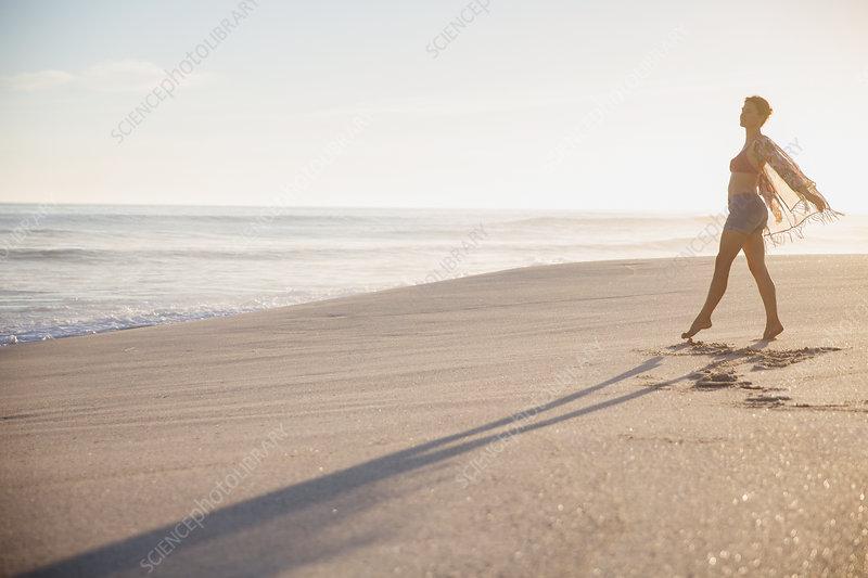 Carefree woman walking on sunny summer ocean beach