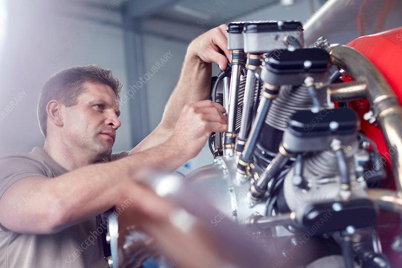 Male airplane mechanic repairing propeller