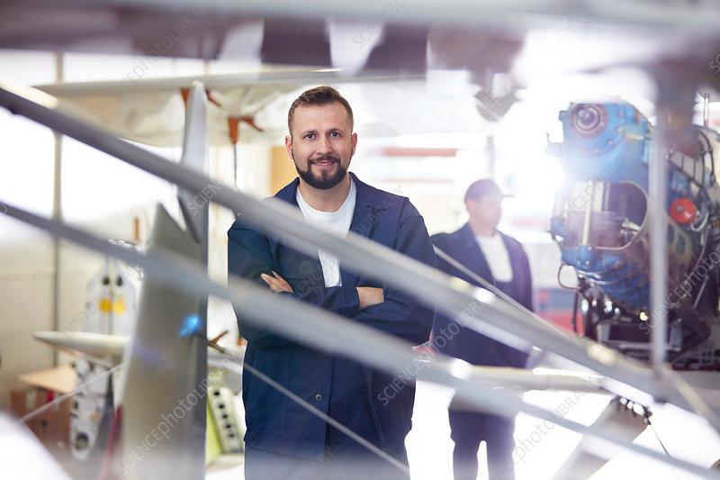 Portrait male airplane mechanic standing