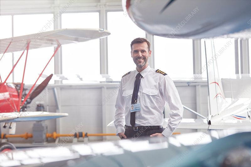 Portrait pilot standing near airplane in hangar