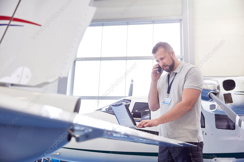 Male airplane mechanic working at laptop
