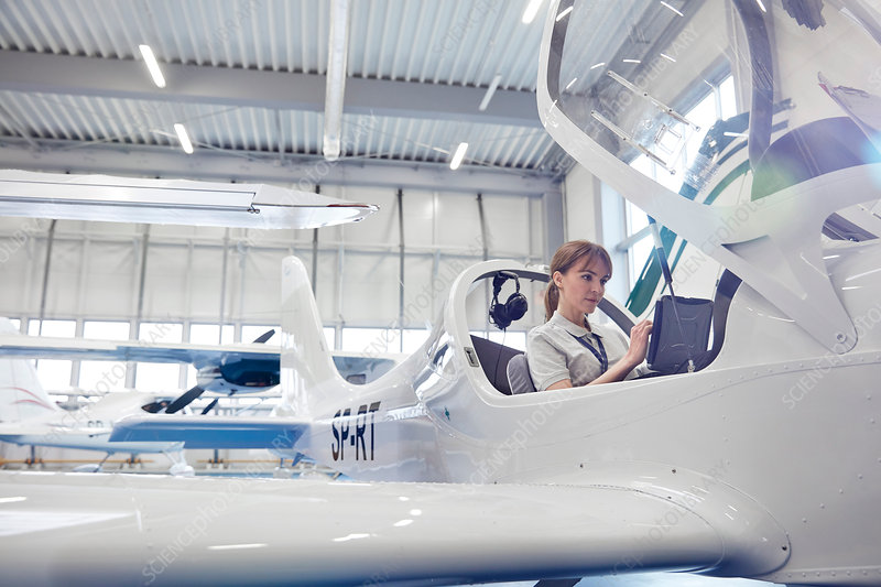 Female pilot in cockpit of small airplane