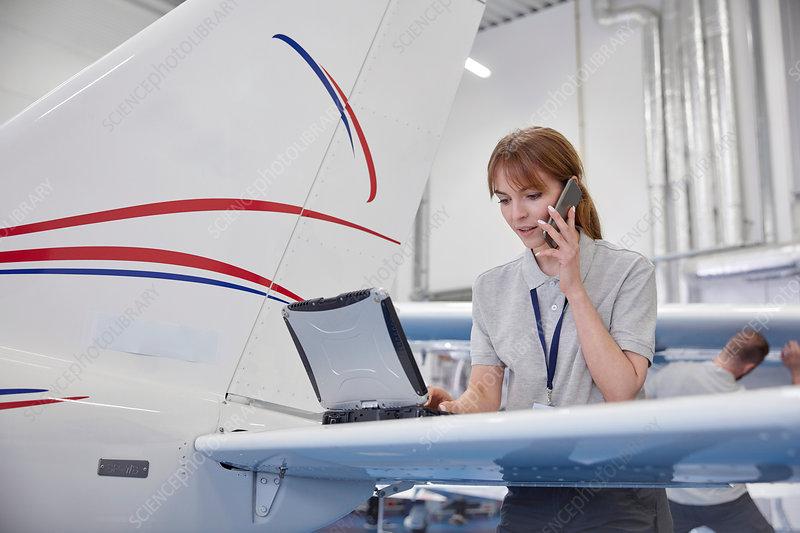 Female airplane engineer working at laptop