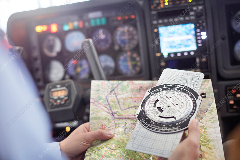 Pilot checking navigational map and compass