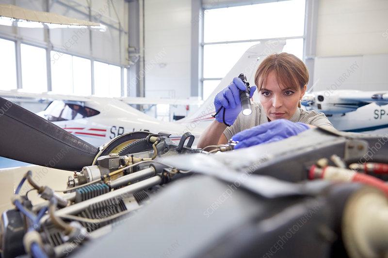 Focused engineer examining airplane engine