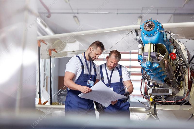 Male engineer mechanics examining plans
