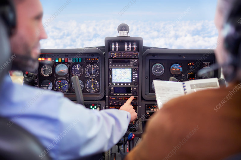 Pilots flying airplane in cockpit
