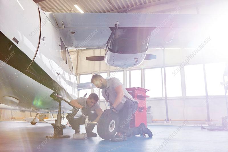 Male mechanics fixing wheels on airplane in hangar