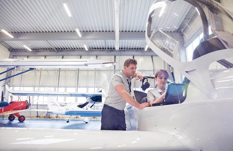 Mechanic engineers working in airplane cockpit