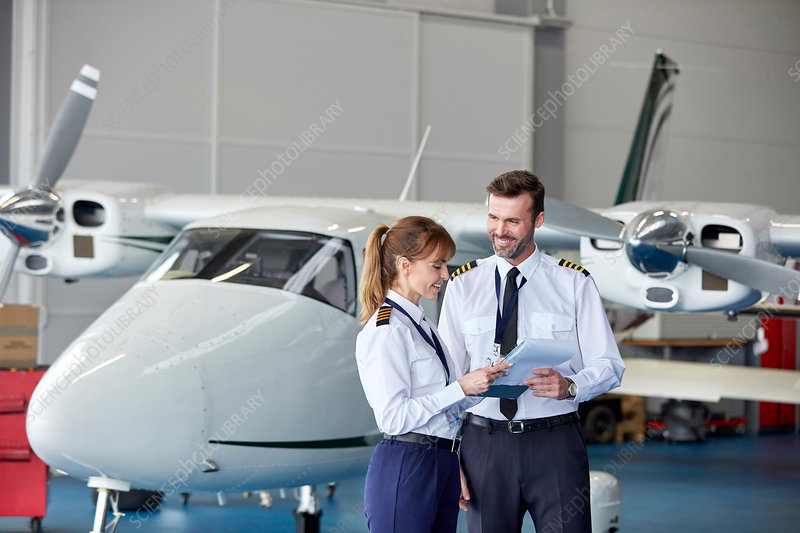 Pilots discussing paperwork near airplane