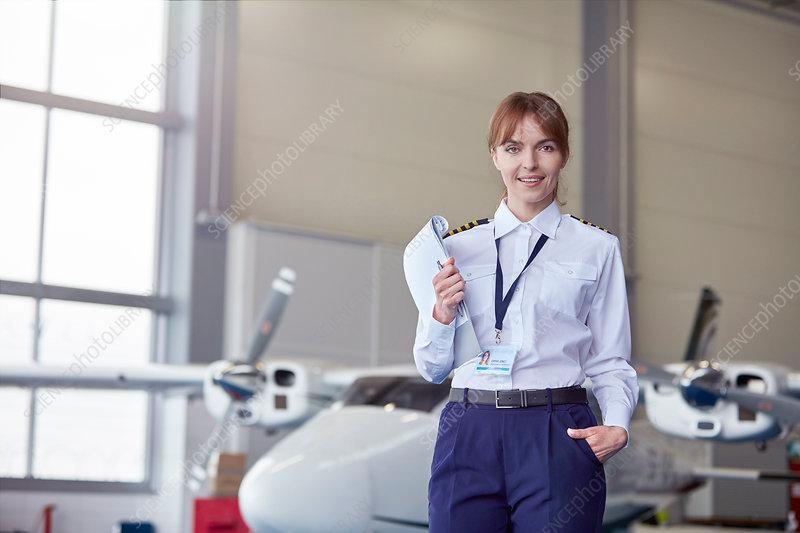 Portrait pilot with paperwork in airplane hangar
