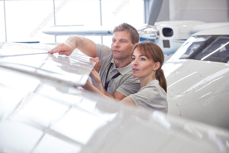 Mechanic engineers examining airplane wing